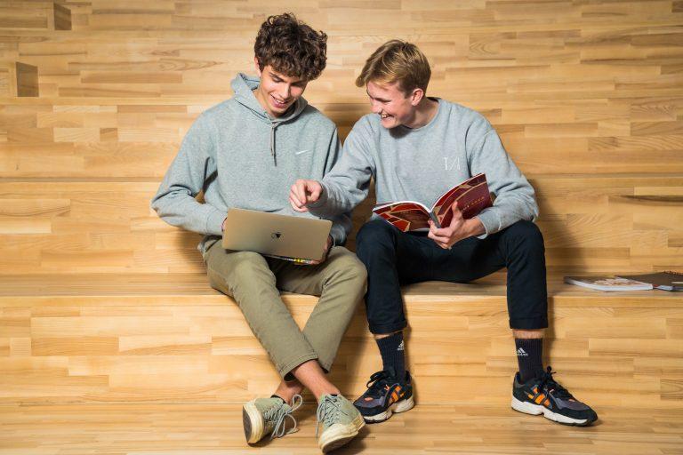 To drenge sidder og samarbejder på en trappe med en computer og en bog